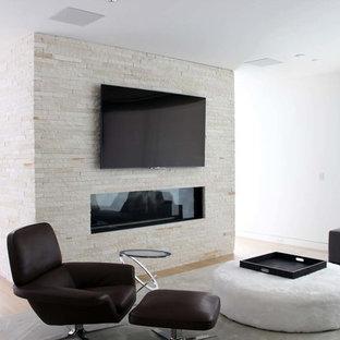 Modelo de salón abierto, moderno, de tamaño medio, con paredes blancas, suelo de madera clara, chimenea lineal, marco de chimenea de piedra, televisor colgado en la pared y suelo azul