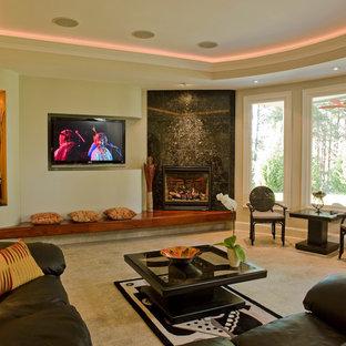 Ejemplo de salón cerrado, minimalista, con paredes beige, moqueta, chimenea de esquina, televisor colgado en la pared y marco de chimenea de piedra