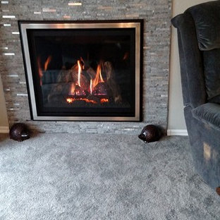デンバーの中サイズのトラディショナルスタイルのおしゃれな独立型リビング (ベージュの壁、カーペット敷き、吊り下げ式暖炉、石材の暖炉まわり、テレビなし) の写真