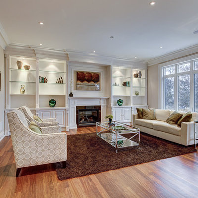Inspiration for a mid-sized transitional formal and open concept medium tone wood floor and brown floor living room remodel in Toronto with beige walls, a standard fireplace, no tv and a stone fireplace