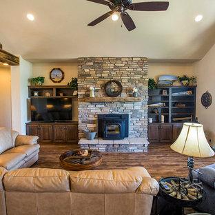 Immagine di un soggiorno stile rurale di medie dimensioni e aperto con sala formale, pareti beige, pavimento in legno massello medio, stufa a legna, cornice del camino in pietra e TV autoportante