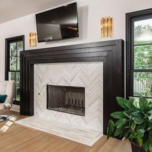 Imagen de salón abierto, minimalista, de tamaño medio, con paredes púrpuras, suelo de madera clara, chimenea tradicional, marco de chimenea de baldosas y/o azulejos y televisor colgado en la pared