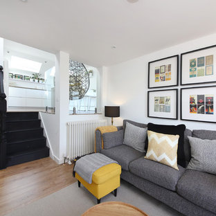 This is an example of a scandi living room in London with white walls and medium hardwood flooring.