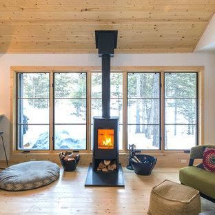 Ispirazione per un piccolo soggiorno nordico aperto con pareti bianche, parquet chiaro, stufa a legna, cornice del camino in metallo, TV a parete e pavimento beige