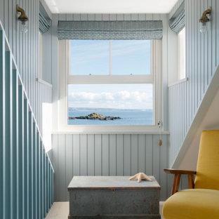 コーンウォールの小さいビーチスタイルのおしゃれなリビングロフト (ライブラリー、青い壁、ラミネートの床、薪ストーブ、テレビなし、茶色い床) の写真