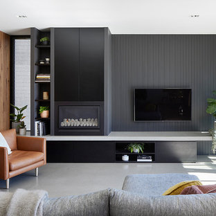 Design ideas for a contemporary enclosed living room in Melbourne with grey walls, concrete floors, a wall-mounted tv and grey floor.