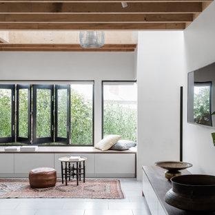 メルボルンの広いコンテンポラリースタイルのおしゃれなリビング (赤い壁、壁掛け型テレビ、グレーの床) の写真