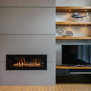 オマハの中くらいのモダンスタイルのおしゃれな独立型リビング (フォーマル、ベージュの壁、淡色無垢フローリング、横長型暖炉、コンクリートの暖炉まわり、テレビなし、茶色い床) の写真