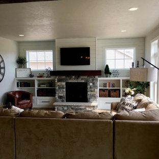 他の地域の中くらいのカントリー風おしゃれなリビング (グレーの壁、クッションフロア、標準型暖炉、石材の暖炉まわり、埋込式メディアウォール、茶色い床) の写真