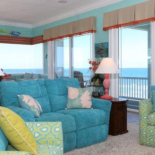 オーランドの中くらいのビーチスタイルのおしゃれなLDK (青い壁、磁器タイルの床、壁掛け型テレビ、ベージュの床、暖炉なし) の写真