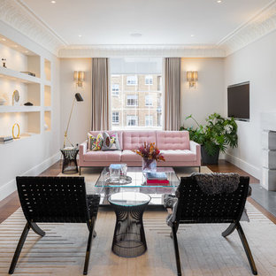 Design ideas for a classic living room in London with white walls, medium hardwood flooring, a standard fireplace, a stone fireplace surround, a wall mounted tv and brown floors.