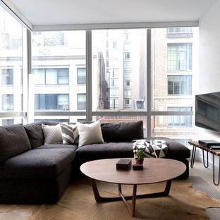 Kleines, Offenes Modernes Wohnzimmer mit weißer Wandfarbe, Laminat und Wand-TV in New York