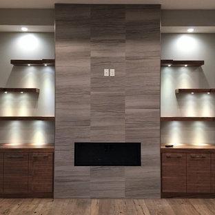 オマハの広いモダンスタイルのおしゃれなLDK (グレーの壁、無垢フローリング、吊り下げ式暖炉、石材の暖炉まわり、壁掛け型テレビ、茶色い床) の写真