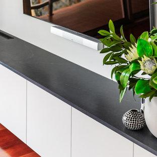 Foto di un soggiorno design di medie dimensioni e aperto con pareti bianche, pavimento in legno massello medio, camino sospeso, cornice del camino in intonaco, TV a parete e pavimento rosso