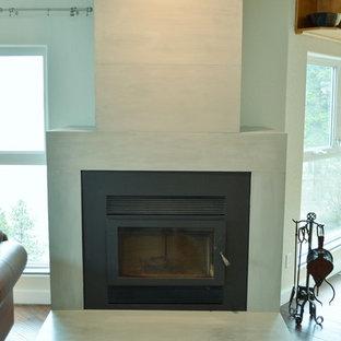 Offenes Modernes Wohnzimmer mit weißer Wandfarbe, braunem Holzboden, Kaminofen und Kaminsims aus Beton in Vancouver