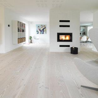 Exemple d'un grand salon scandinave ouvert avec un sol en bois clair, cheminée suspendue et un manteau de cheminée en bois.