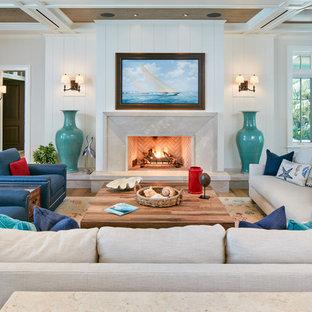 デンバーの大きいビーチスタイルのおしゃれな独立型リビング (白い壁、淡色無垢フローリング、標準型暖炉、茶色い床、コンクリートの暖炉まわり、テレビなし) の写真
