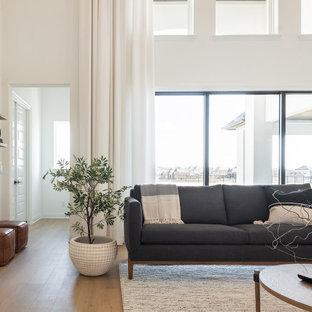 Ispirazione per un grande soggiorno moderno aperto con pareti bianche, parquet chiaro, camino classico, cornice del camino in intonaco, TV a parete e pavimento beige