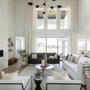広いトランジショナルスタイルのおしゃれなLDK (白い壁、淡色無垢フローリング、漆喰の暖炉まわり、ベージュの床、横長型暖炉) の写真