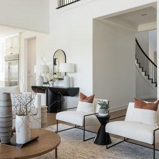 Modelo de salón abierto, minimalista, grande, con paredes blancas, suelo de madera clara, chimenea tradicional, marco de chimenea de yeso, televisor colgado en la pared y suelo beige