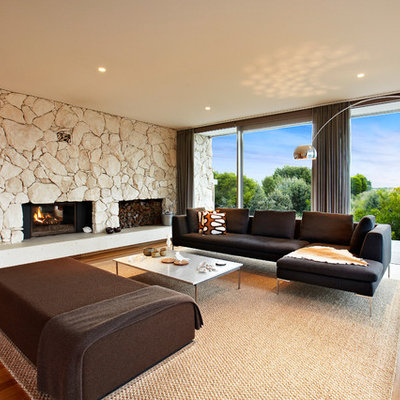 Example of a large 1960s formal and open concept medium tone wood floor living room design in Melbourne with a standard fireplace and a stone fireplace