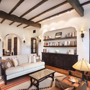 Aménagement d'un salon avec une bibliothèque ou un coin lecture sud-ouest américain de taille moyenne avec un mur blanc, un sol en bois brun, une cheminée standard, un manteau de cheminée en plâtre et aucun téléviseur.