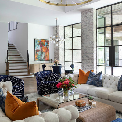 Example of a huge transitional open concept medium tone wood floor and brown floor living room design in Houston with a bar, white walls, a standard fireplace and a stone fireplace