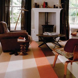 Modelo de salón abierto, tradicional, de tamaño medio, con paredes blancas, suelo de linóleo, estufa de leña y marco de chimenea de baldosas y/o azulejos