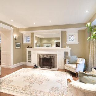 Foto di un soggiorno vittoriano di medie dimensioni e chiuso con sala formale, pareti gialle, pavimento in legno massello medio, camino classico e cornice del camino in cemento