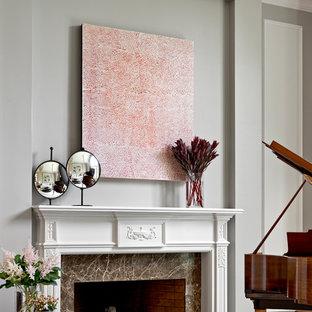 ナッシュビルの広いトラディショナルスタイルのおしゃれな独立型リビング (ミュージックルーム、マルチカラーの壁、無垢フローリング、標準型暖炉、石材の暖炉まわり、テレビなし、茶色い床) の写真