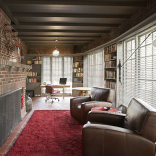 Mid-sized urban open concept brick floor and red floor living room library photo in New York with a standard fireplace, a brick fireplace, red walls and no tv