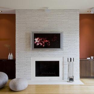Ejemplo de salón contemporáneo con chimenea tradicional y televisor colgado en la pared
