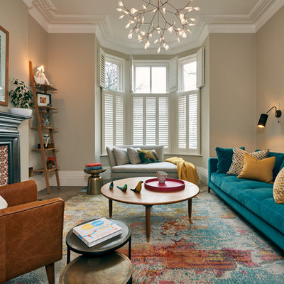 Living room - mid-sized contemporary enclosed medium tone wood floor and brown floor living room idea in London with beige walls, a standard fireplace, a metal fireplace and no tv