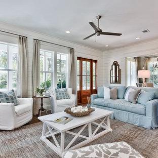 マイアミの大きいビーチスタイルのおしゃれなLDK (白い壁、標準型暖炉、無垢フローリング、壁掛け型テレビ) の写真