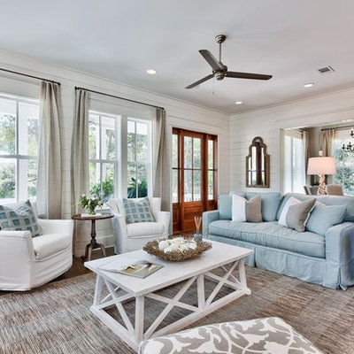 Large beach style open concept medium tone wood floor living room photo in Miami with white walls, a standard fireplace and a wall-mounted tv