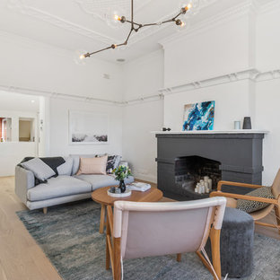 Photo of a scandinavian formal living room in Perth with white walls, light hardwood floors, a standard fireplace and no tv.