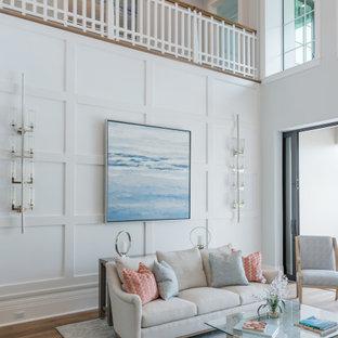 Ispirazione per un soggiorno chic aperto con pareti bianche, pavimento in legno massello medio e pavimento marrone