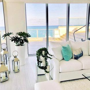 マイアミの広いビーチスタイルのおしゃれなLDK (フォーマル、白い壁、磁器タイルの床、暖炉なし、テレビなし、グレーの床) の写真