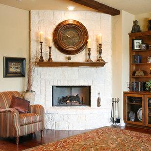 Foto de salón para visitas abierto, clásico, de tamaño medio, con paredes beige, suelo de madera en tonos medios, pared multimedia, chimenea de esquina y marco de chimenea de piedra