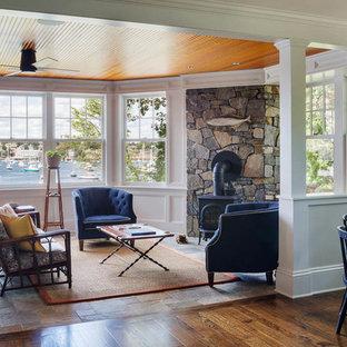 Immagine di un soggiorno american style di medie dimensioni e aperto con sala formale, pareti bianche, pavimento in ardesia, stufa a legna, cornice del camino in pietra e nessuna TV