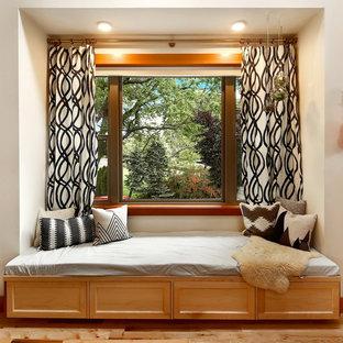Immagine di un soggiorno american style aperto con pareti bianche, parquet chiaro e TV a parete