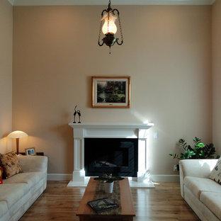 Modelo de salón para visitas cerrado, minimalista, de tamaño medio, con paredes marrones, suelo laminado, chimenea tradicional, marco de chimenea de madera y suelo multicolor