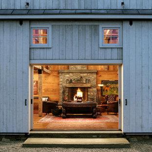 Imagen de salón para visitas de estilo de casa de campo, de tamaño medio, con suelo de madera en tonos medios, chimenea tradicional, marco de chimenea de piedra y paredes marrones