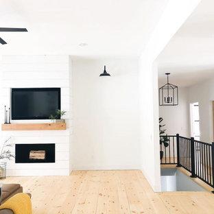 На фото: большая гостиная комната в стиле кантри с белыми стенами, светлым паркетным полом, стандартным камином, фасадом камина из вагонки и мультимедийным центром