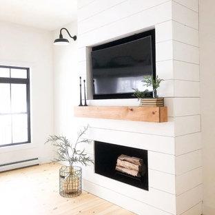 Immagine di un soggiorno country aperto con pareti bianche, parquet chiaro, camino lineare Ribbon, cornice del camino in legno, parete attrezzata e pavimento beige