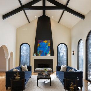 Modelo de salón para visitas abierto, clásico renovado, grande, sin televisor, con suelo de madera clara, chimenea tradicional, marco de chimenea de piedra, paredes beige y suelo marrón