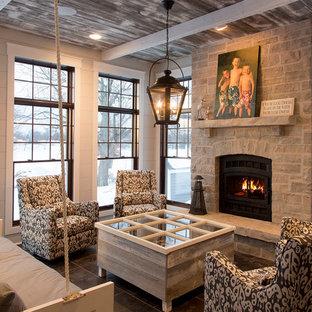 Ispirazione per un grande soggiorno american style chiuso con pareti grigie, pavimento in ardesia, camino classico, cornice del camino in pietra e nessuna TV