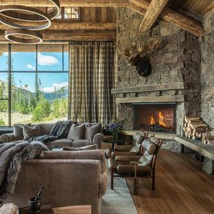 Modelo de salón para visitas abierto, rural, grande, sin televisor, con paredes marrones, suelo de madera en tonos medios, chimenea de esquina, marco de chimenea de piedra y suelo marrón