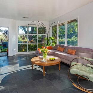 Ispirazione per un soggiorno minimalista di medie dimensioni e aperto con pareti blu, pavimento in ardesia, nessun camino e TV a parete
