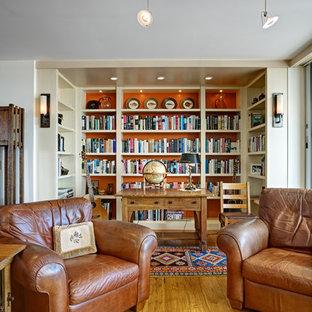 Immagine di un soggiorno bohémian di medie dimensioni e aperto con libreria, pareti bianche, pavimento in legno massello medio, parete attrezzata e pavimento giallo
